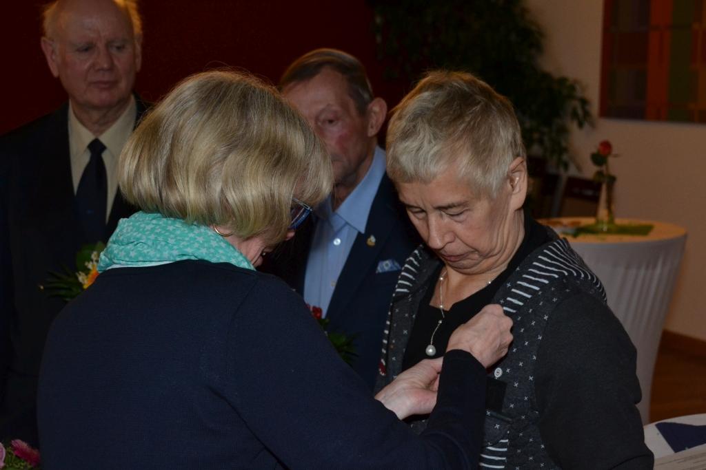Eine Frau steckt einer anderen Frau ein Ehrenzeichen ans Revers