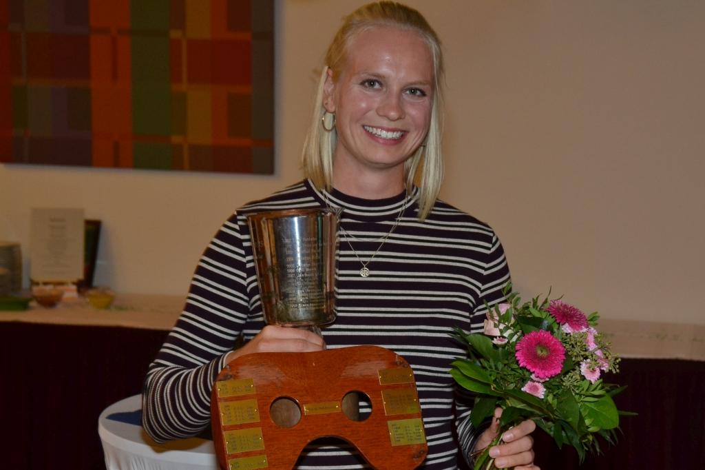 lachende Frau hält Pokal, Rudersitz und Blumen in der Hand