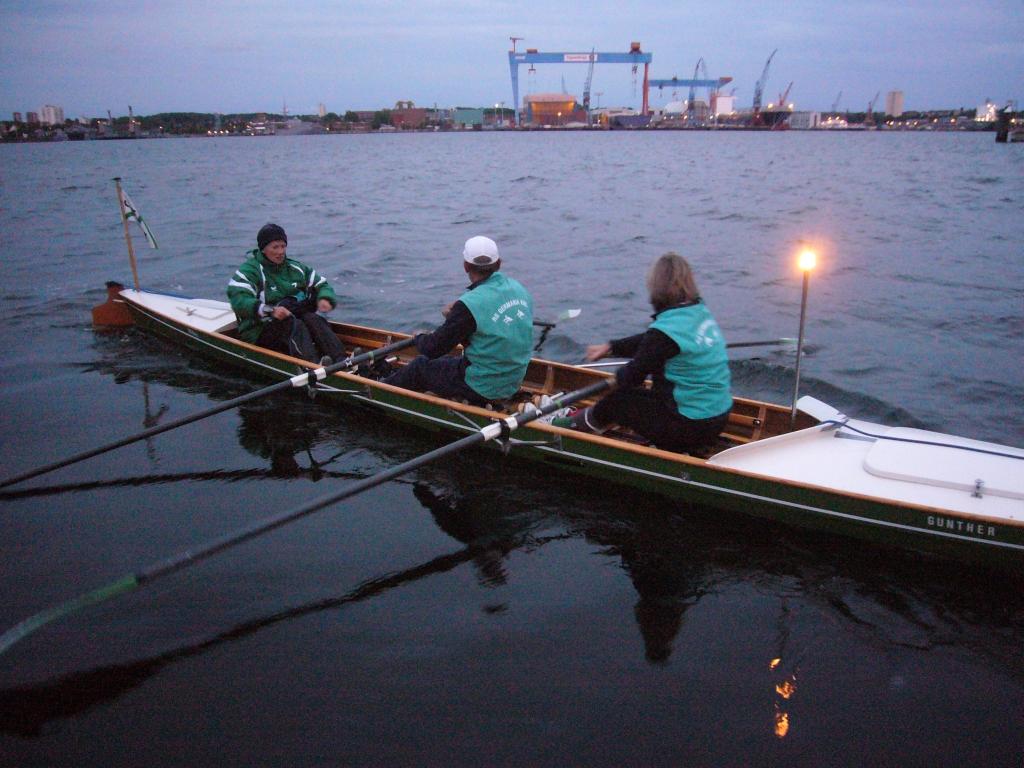 gesteuertes Ruderboot mit Rundumleuchte im Hintergrund die Portalkräne von German Naval Yards