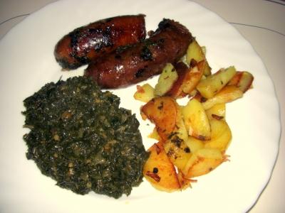Teller mit Grünkohl, Kochwurst und Bratkartoffeln