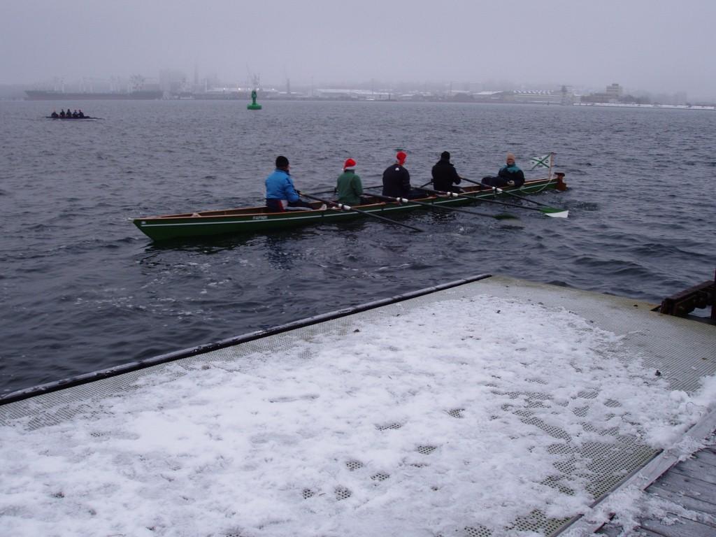 Ruderer bei Eis und Schnee im Ruderboot auf dem Wasser