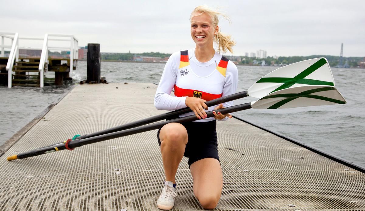 U19-Vizeeuropameisterin Frieda Hämmerling kniet auf dem Bootssteg der RG Germania mit Ruderskulls in den HändenMai 2014 in Hazewinkel (Belgien)