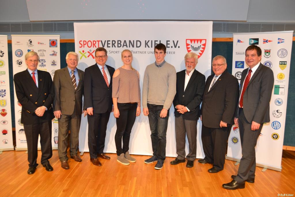 Gruppenbild mehrerer männlicher Personen in ihrer Mitte eine junge Frau vor dem Banner des Sportverbands Kiel