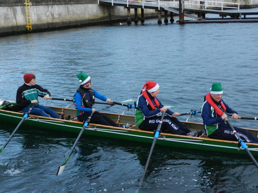 Vier Ruderer in einem Ruderboot mit Weihnachtsmütze auf dem Kopf