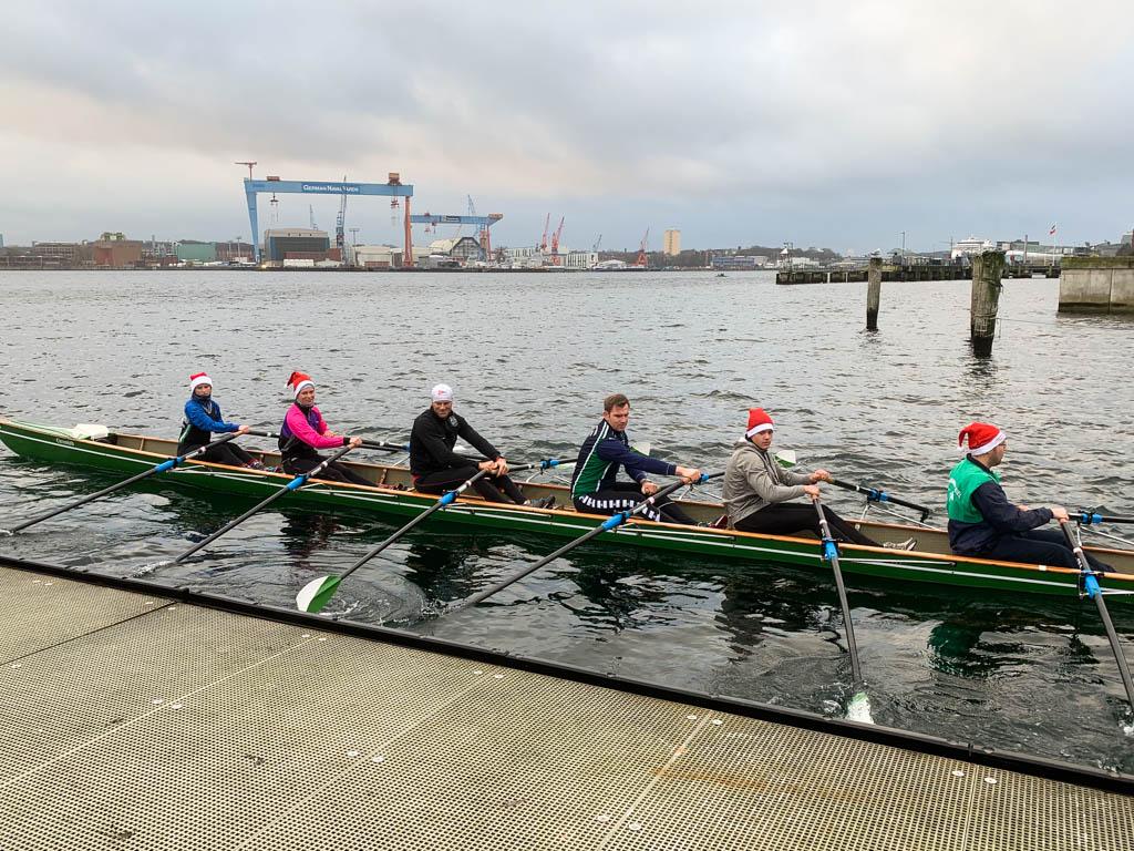 sechs Ruderer mit Weihnachtsmütze in einem Ruderboot vor einem Bootssteg