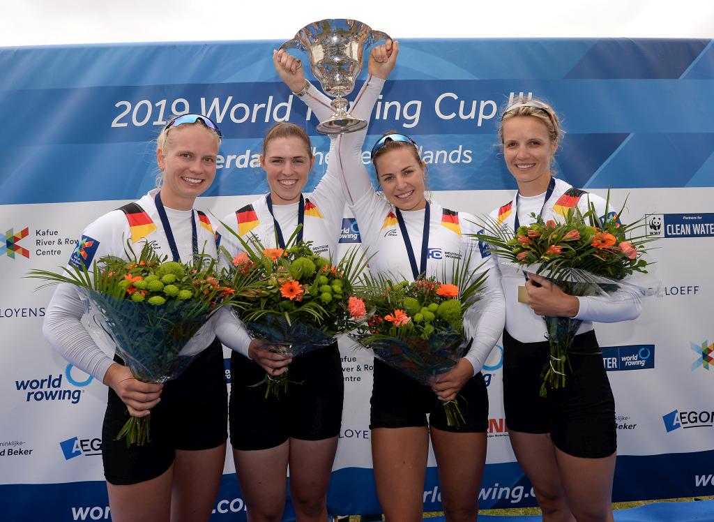 vier Ruderrinnen halten bei der Siegerehrung des Frauen-Doppelvierer lachend ihren gewonnenen Pokal in die Höhe