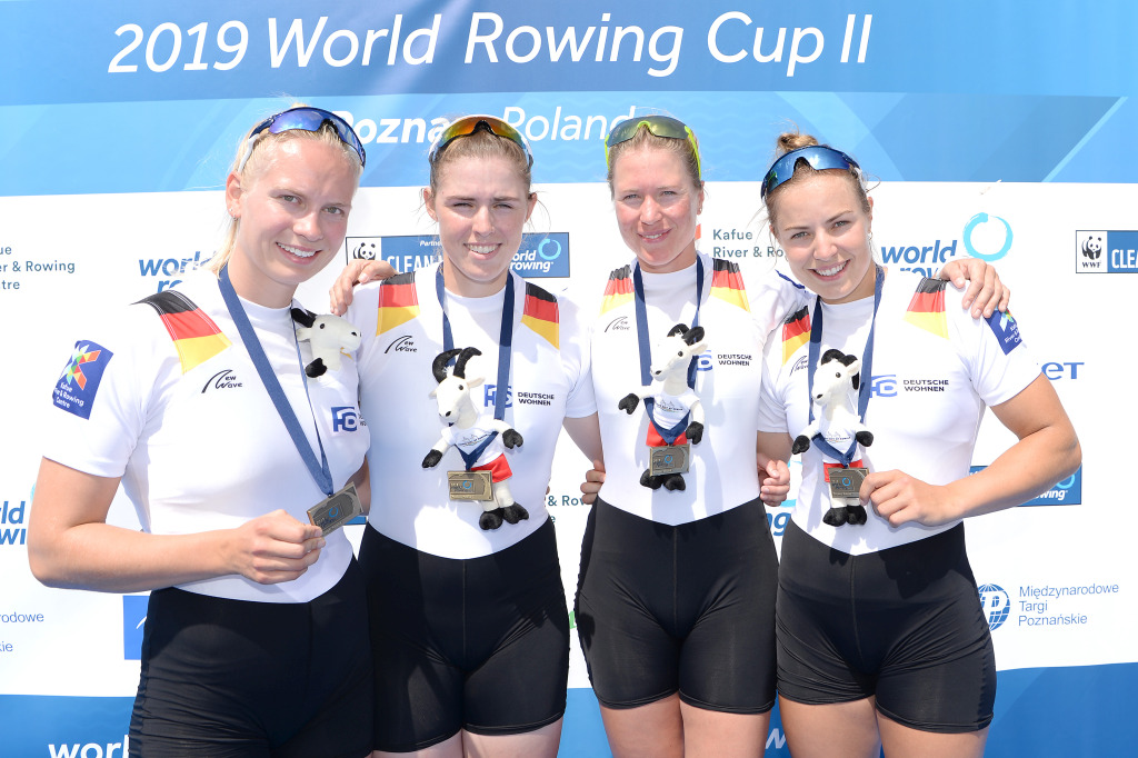 vier Ruderrinnen mit Bronzemedaille um den Hals lächeln bei der Siegerehrung im Frauen-Doppelvierer in die Kamera