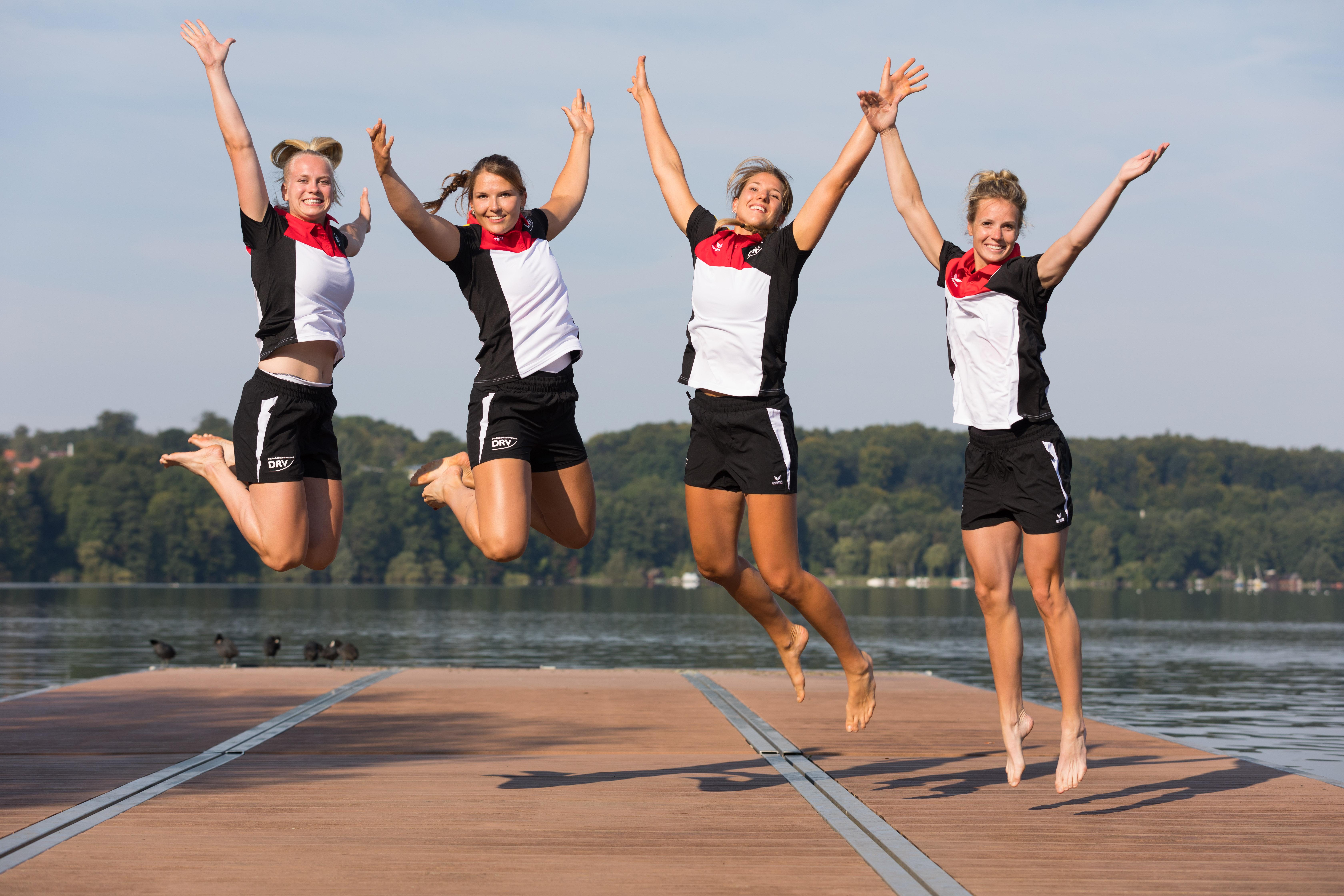 Vier junge Frauen in Sportkleidung springen auf einem Steg in die Höhe