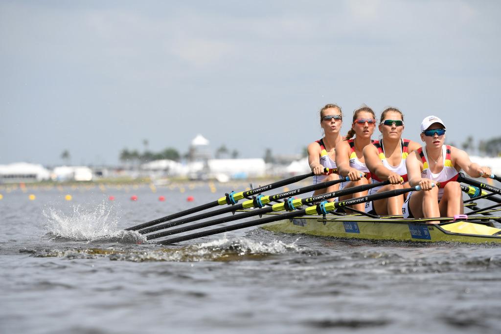 Vier Ruderinnen in einem gelben Ruderboot mit Skulls in den Händen