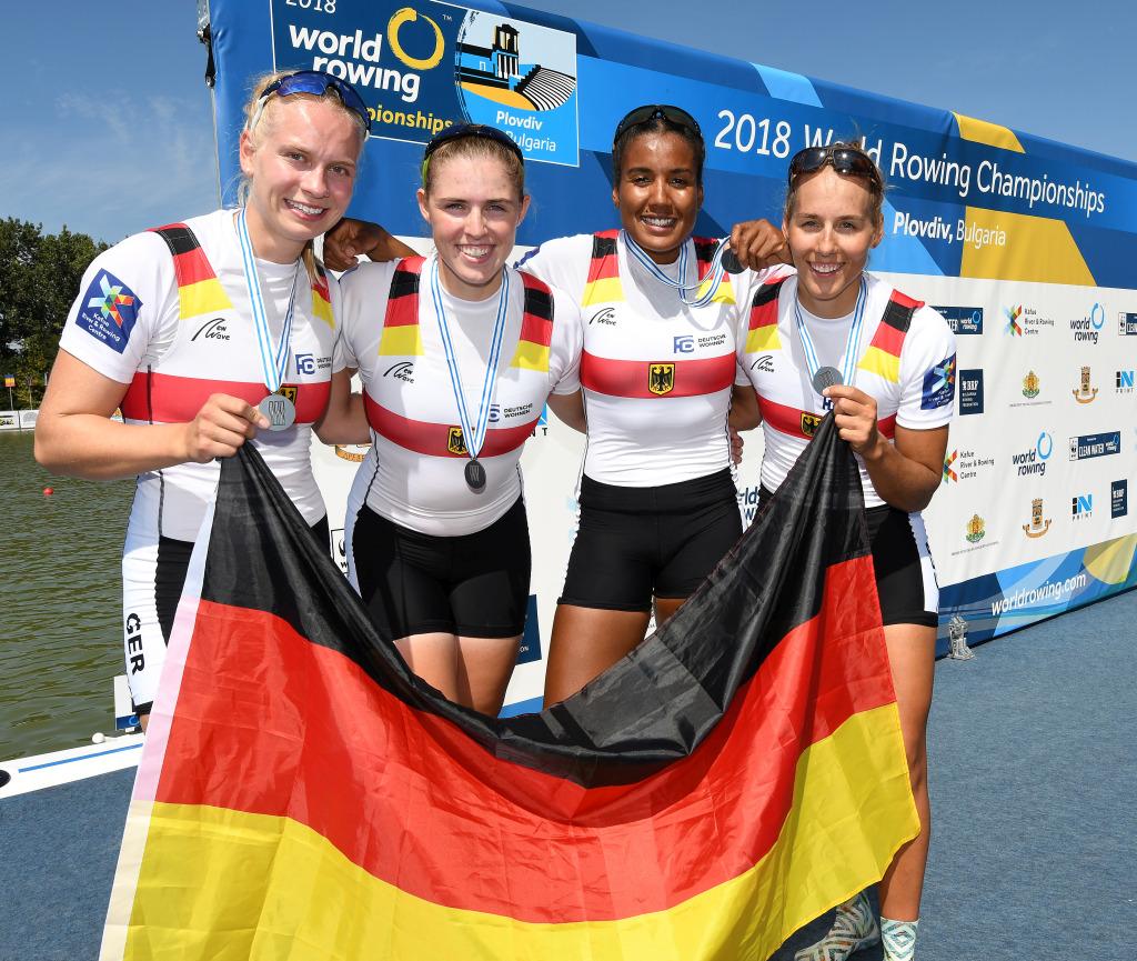 Vier Frauen nebeneinander im Ruderdress, die eine Deutschlandfahne halten, freuen sich über die Silbermedaille die sie um den Hals tragen