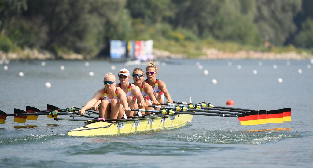Vier Frauen im Ruderboot halten die in den Deutschlandfarben schwarz, rot, gold gestrichenen Ruderblätter aufrecht