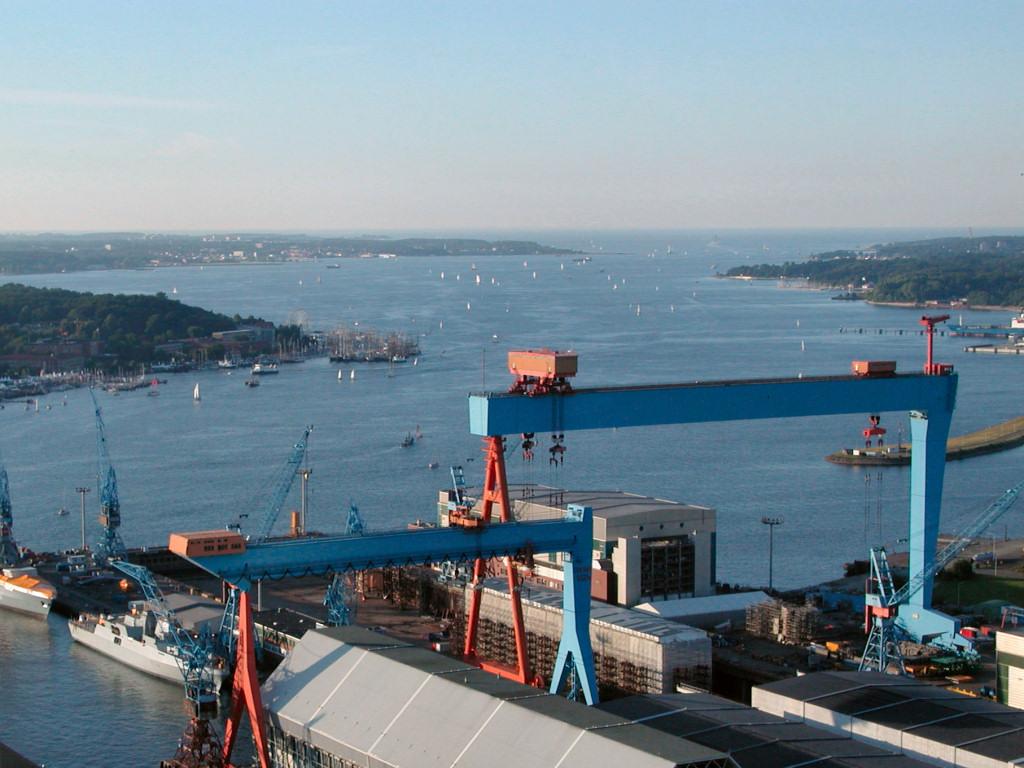 Kieler Förde mit Blickrichtung nach Norden zur Ostsee, im Vordergrund die Portalkräne der HDW-Werft.