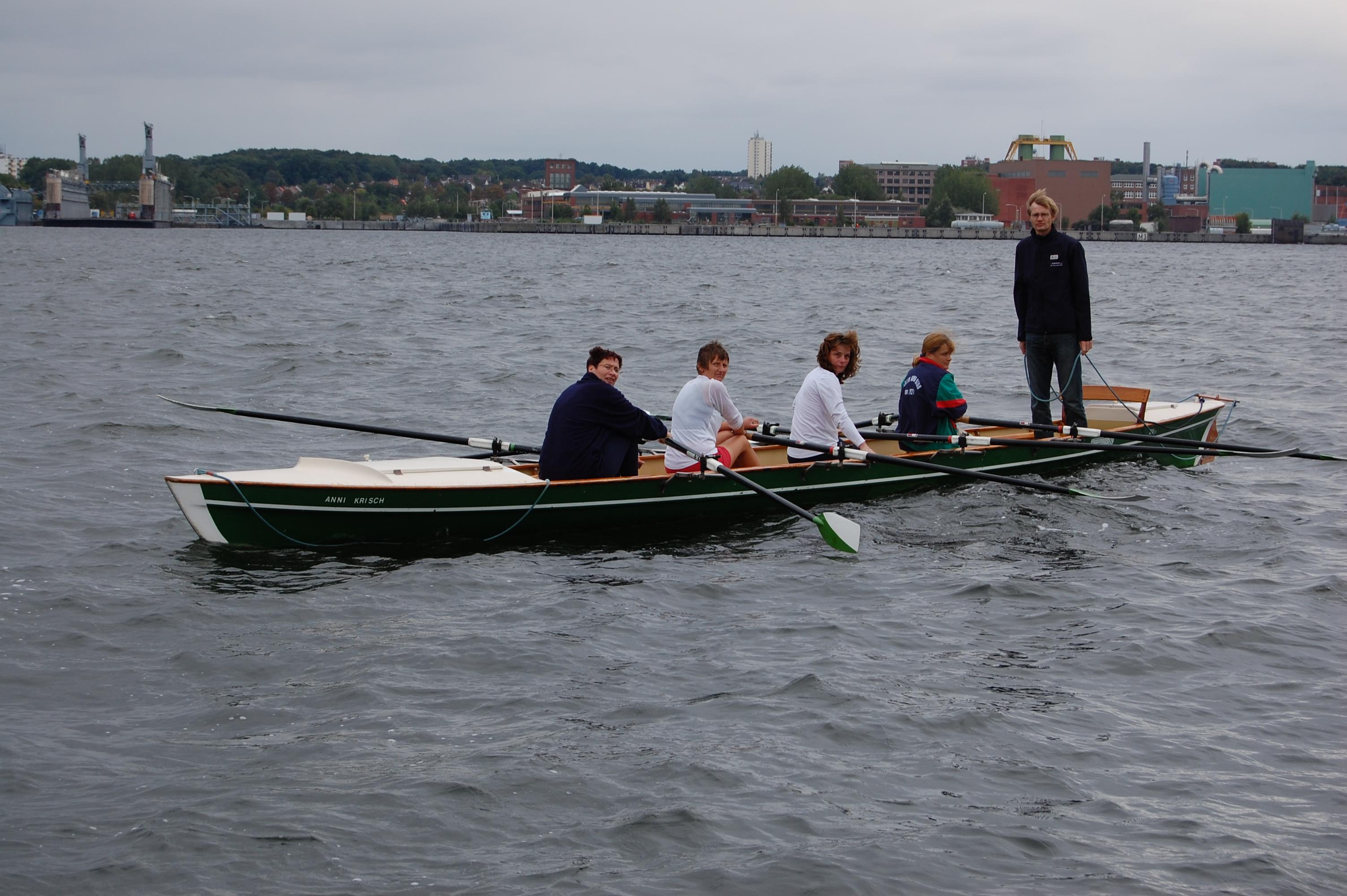Übungsleiter vermittelt im Ruderboot stehend vier Ruderern die Ruder-Technik