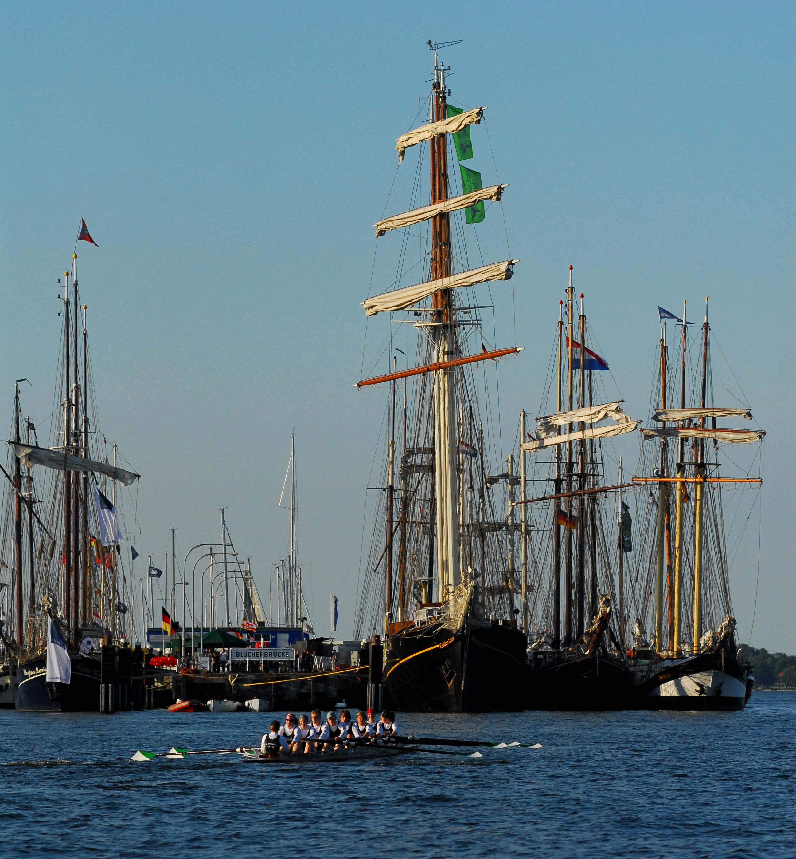 Rennachter vor historischen Schiffen