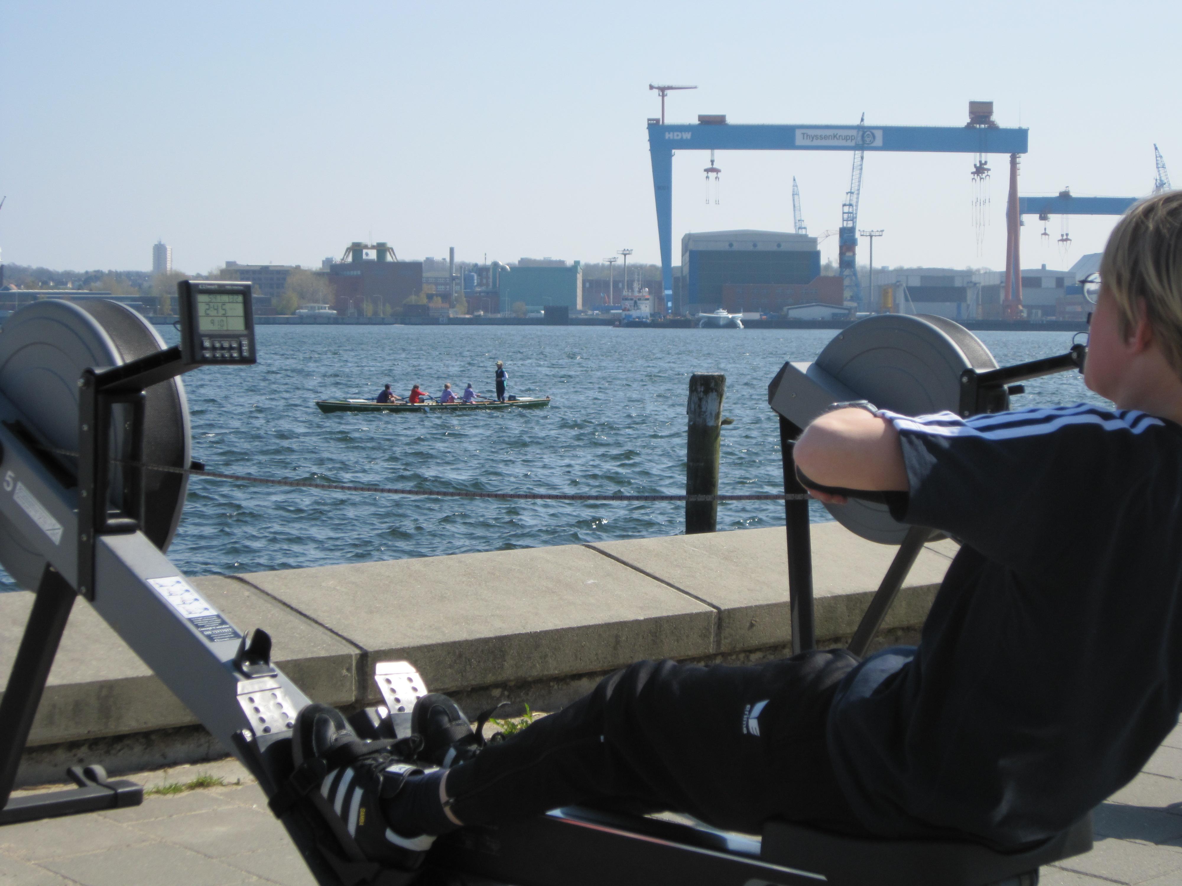 Kind auf dem Ergometer, im Hintergrund Kinder im Ruderboot vor dem Portalkran von German Naval Yards