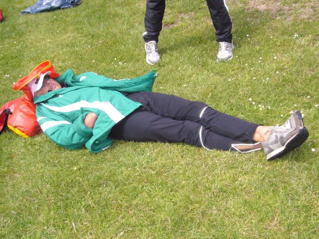 Ein Mann in grüner Jacke mit weißen Streifen liegt schlafend auf dem Rasen mit dem Kopf auf roten Beuteln