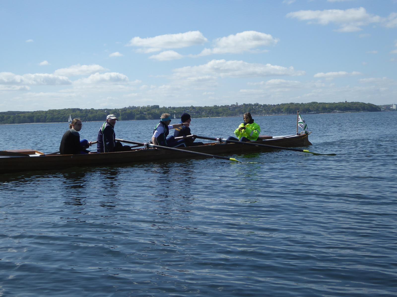 ein Ruderboot schwimmt auf dem Wasser mit fünf Personen darin, im Hintergrund eine Baumreihe am Ufer