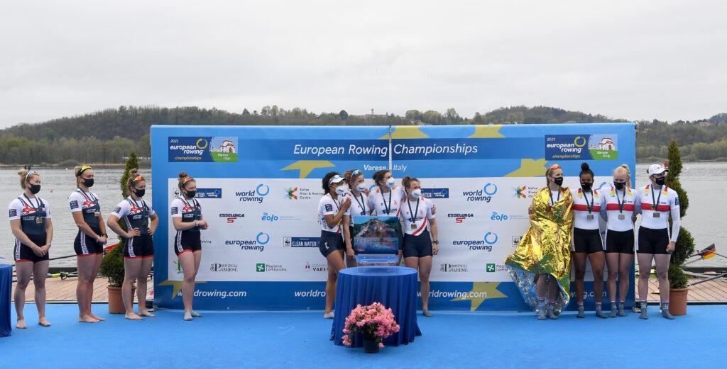 Drei Frauengruppen stehen mit Abstand bei einer Siegerehrung vor einem großen Plakat.