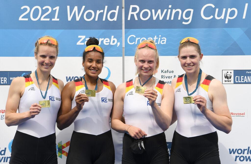 Vier Frauen im Sporttrikot stehen nebeneinander vor einer Plakatwand und halten Goldmedaillen in der Hand