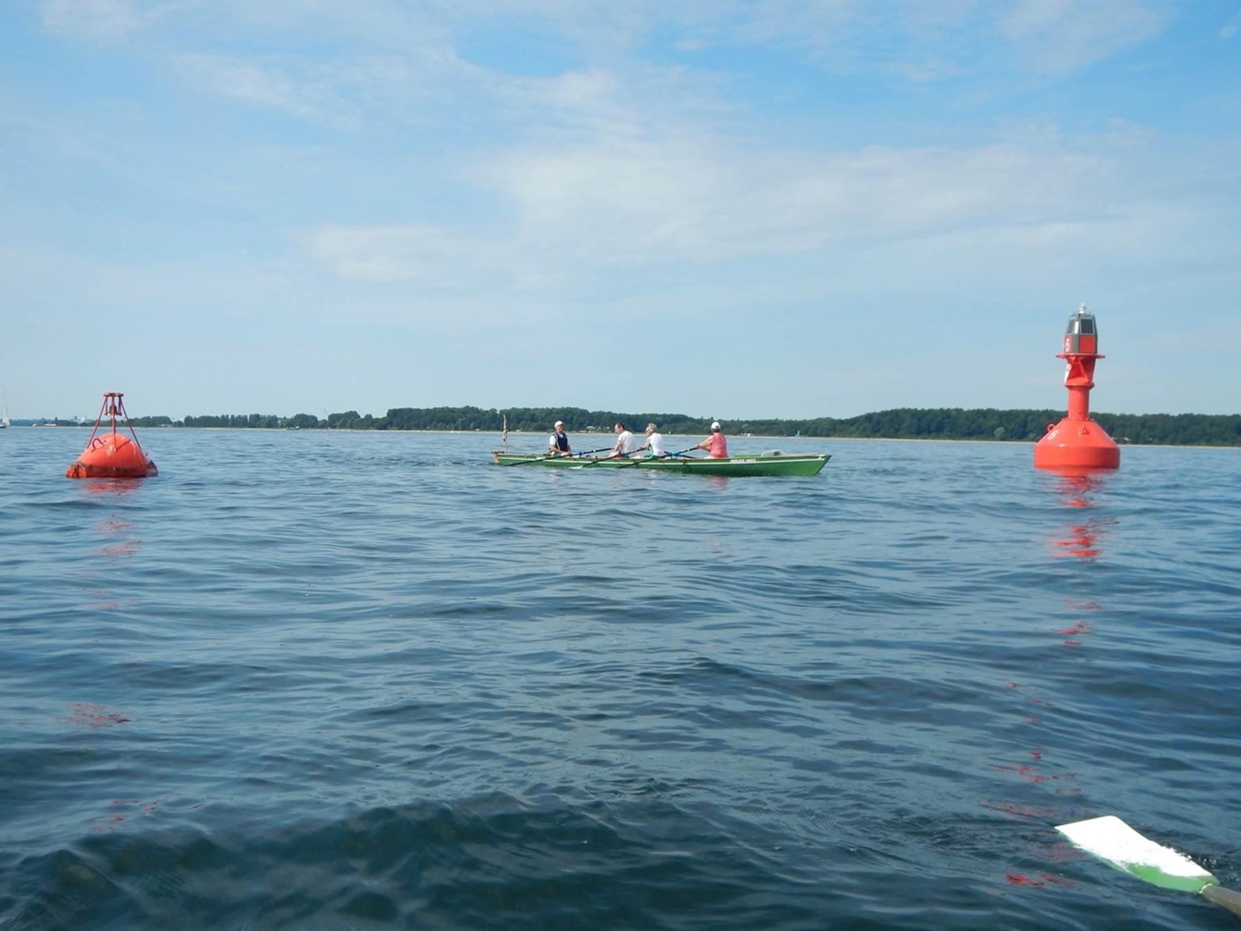 Vier Personen in einem Ruderboot, dass auf dem Wasser zwischen zwei roten Tonnen liegt